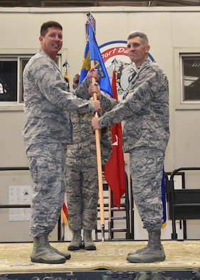 Col. Timrek Heisler, 521st Air Mobility Operations Group commander, passes the guidon to Lt. Col. Nathan Mansfield, 728th Air Mobility Squadron commander, during the 728th AMS change of command ceremony June 9, 2016, at Incirlik Air Base, Turkey. A change of command ceremony is a tradition that represents a formal transfer of authority and responsibility from the outgoing commander to the incoming commander. (U.S. Air Force photo by Airman 1st Class Devin M. Rumbaugh/Released)