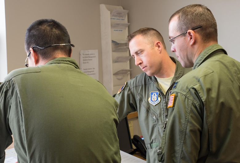 Maj. Ethan Bryant and Capt. Mike McFadden, pilots from the 96th Airlift Squadron, go over their pre-flight plans with Senior Master Sgt. Thomas Kim. (U.S. Air Force photo by Master Sgt. Eric Amidon)