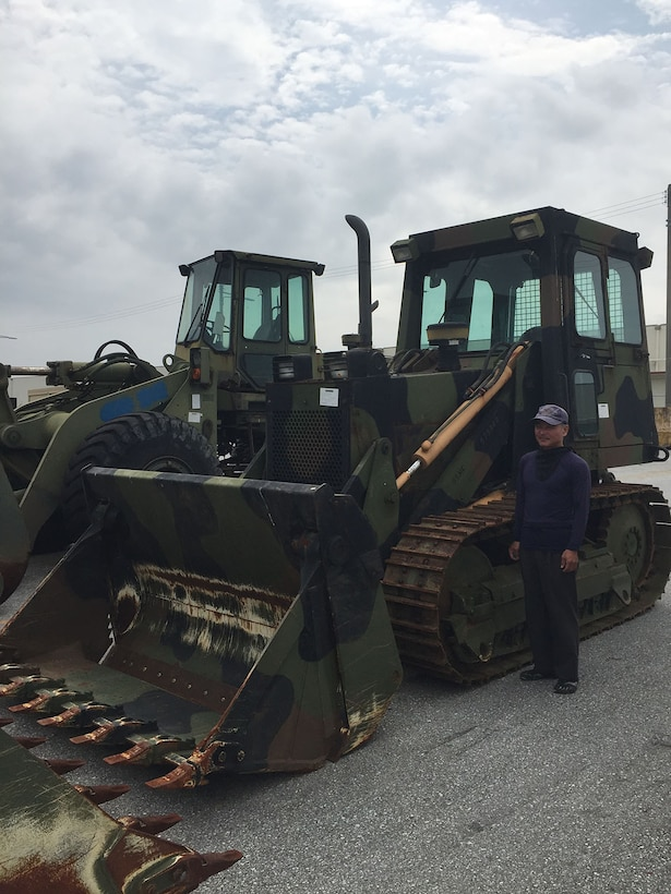 Satoru Matsuda, a forklift operator at DLA Disposition Services at Okinawa looks over one of the extra-large items that had to arrive late at night to meet local road restrictions.