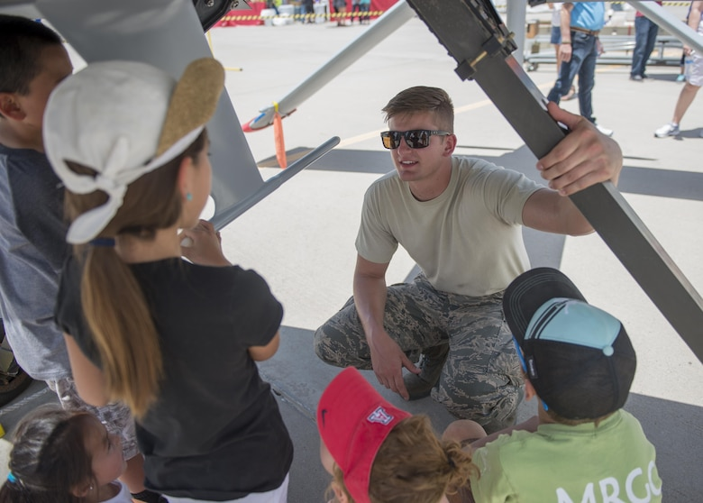 Senior Airman Alex, a 9th Aircraft Maintenance Unit crew chief at Holloman Air Force Base, N.M., tells children about some of the components found underneath an MQ-1 at the Kirtland AFB Open House on June 5. Over 50,000 people visited the Kirtland AFB Air Show on June 4 and 5. Holloman Airmen had the opportunity to display an MQ-1 Predator and answer questions visitors had about RPAs and their mission at Holloman. (Last names are being withheld due to operational requirements. U.S. Air Force photo by Airman 1st Class Randahl J. Jenson)