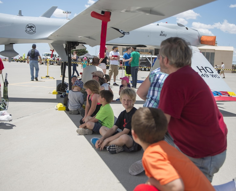 Visitors at the Kirtland Air Force Base Air Show rest in the shade of an MQ-1 Predator on June 5. Over 50,000 people visited the Kirtland AFB Open House June 4 and 5. Holloman Airmen had the opportunity to display an MQ-1 Predator and answer questions visitors had about RPAs and their mission at Holloman. (U.S. Air Force photo by Airman 1st Class Randahl J. Jenson)