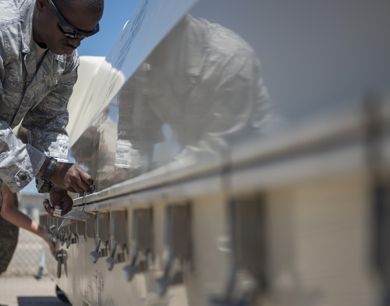 Master Sgt. Robert, a 9th Aircraft Maintenance Unit specialist section chief at Holloman Air Force Base, N.M., unlatches the container housing an MQ-1 Predator at Kirtland AFB on June 3. Over 50,000 people visited the Kirtland AFB Open House on June 4 and 5. Holloman Airmen had the opportunity to display an MQ-1 Predator and answer questions visitors had about RPAs and their mission at Holloman. (Last names are being withheld due to operational requirements. U.S. Air Force photo by Airman 1st Class Randahl J. Jenson)