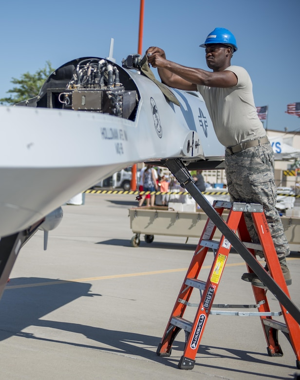 Staff Sgt. Omoro, a 9th Aircraft Maintenance Unit demo team leader at Holloman Air Force Base, N.M., assembles an MQ-1 Predator for the Kirtland AFB Open House on June 4. Holloman Airmen were able to fully construct the model MQ-1 Predator from a cargo container in 31 minutes. (Last names are being withheld due to operational requirements. U.S. Air Force photo by Airman 1st Class Randahl J. Jenson)