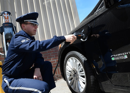 Senior Airman Alec Cope, a ceremonial guardsman with the Patriot Honor Guard, plugs in a hybrid vehicle at Hanscom Air Force Base, Mass., June 2, 2016. The 66th Logistics Readiness Squadron recently unveiled the plug-in electric hybrid vehicle and charging station during an open house. The vehicle complies with President Barack Obama's federal government directive to become more energy efficient with the Defense Department's vehicle fleet. (U.S. Air Force photo/Linda LaBonte Britt)