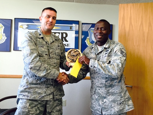 Staff Sgt. Olorunyomi Martins, an Individual Mobilization Augmentee paralegal at the 436th Airlift Wing legal office, is presented the Staff Judge Advocate of the Month Award by Lt. Col. Thomas P. Condie, the 436th Airlift Wing SJA.