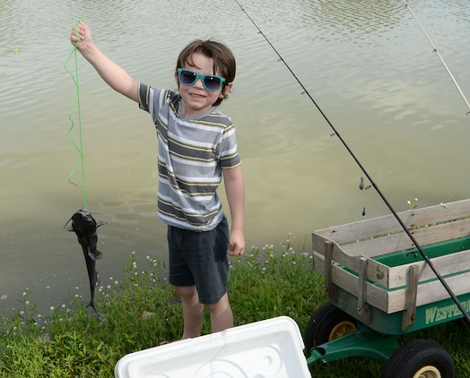Four-year old Gavin Frakes shows off the catfish, which wins him a trophy at the 28th Annual Buddy Fishing Tournament at Marine Corps Logistics Base Albany, June 4. At the weigh in, Gavin walked away as the event's overall biggest catch-of-the-day winner with his 1.4 pound catfish.