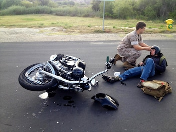 Seaman Max Norum, a corpsman with 1st Supply Battalion, Headquarters and Support Company treats Sgt. Brandon Jackson for injuries sustained in a motorcycle accident aboard Camp Pendleton, Calif., May 23, 2016. Jackson, an airframes mechanic instructor at the Center for Naval Aviation Technical Training, was on his daily commute to work when he collided with a passenger vehicle. He sustained only minor injuries in the accident. (Courtesy Photo)