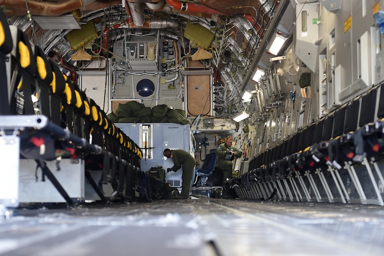 Staff Sgt. Seth Lewis (left) and Senior Airman Mike Longo (right), 7th Airlift Squadron C-17 Globemaster III loadmasters, conduct pre-flight check lists at Pope Army Air Field, North Carolina, June 4, 2016. Seven C-17's air dropped more than 600 Soldiers over the Pope Army Airfield Range for training. (U.S. Air Force photo/Staff Sgt. Naomi Shipley)