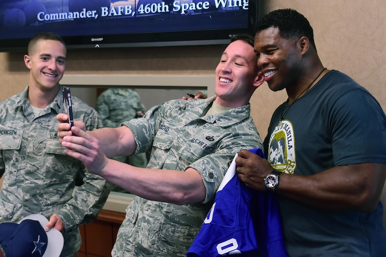 Tech. Sgt. Michael Boyd, 460th Space Wing commander's action group, takes a selfie with Herschel Walker, former National Football League running back, June 8, 2016, at the wing headquarters building on Buckley Air Force Base, Colo. Walker visited Buckley to show his appreciation for military members and speak about his own life experiences. (U.S. Air Force photo by Airman 1st Class Luke W. Nowakowski/Released)