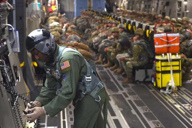 Staff Sgt. Seth Lewis, 7th Airlift Squadron C-17 loadmaster, conducts a communications check during an air drop over the Pope Army Air Field Range, North Carolina, June 4, 2016. Loadmasters are responsible for loading, securing and escorting cargo and passengers as well as calculating weight distribution. (U.S. Air Force photo/Staff Sgt. Naomi Shipley)