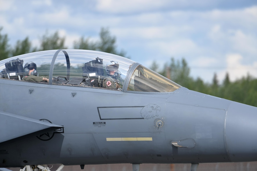 A U.S. Air Force F-15E Strike Eagle pilot and weapon systems officer assigned to the 494th Fighter Squadron out of Royal Air Force Lakenheath, England, look over as they taxi down the Eielson Air Force Base, Alaska, flight line in their all-weather, highly maneuverable, dual-role fighter June 6, 2016, during RED FLAG-Alaska (RF-A) 16-2. RF-A is a series of Pacific Air Forces commander-directed field training exercises that provides unique opportunities to integrate various forces like the Liberty Wing into joint, coalition and multilateral training from simulated forward operating bases. (U.S. Air Force photo by Master Sgt. Karen J. Tomasik/Released)