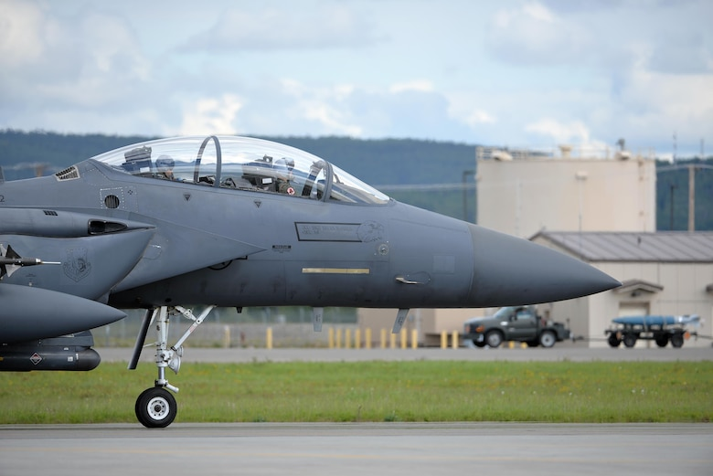 A U.S. Air Force F-15E Strike Eagle all-weather, highly maneuverable, dual-role fighter assigned to the 494th Fighter Squadron out of Royal Air Force Lakenheath, England, taxis down the Eielson Air Force Base, Alaska, flight line as an Airman transports a dummy munition in the background, June 6, 2016, during RED FLAG-Alaska (RF-A) 16-2. RF-A enables joint and international units like the Liberty Wing to sharpen their combat skills by flying simulated combat sorties in a realistic threat environment, which allows them to exchange tactics, techniques and procedures while improving interoperability. (U.S. Air Force photo by Master Sgt. Karen J. Tomasik/Released)