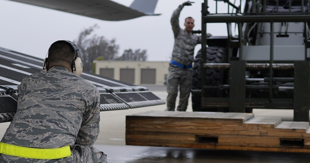 Tech. Sgt. Kenneth Cumbie, 30th Logistics Readiness Squadron air terminal section chief, and Staff Sgt. Nickolas Jordan, 30th LRS air terminal NCOIC, guide a forklift to place a ramp behind the C-17 Globemaster III, May 19, 2016, Vandenberg Air Force Base, Calif. The air terminal at Vandenberg may not have the fast-paced tempo of an aircraft-centric base, but the items they move with their small crew tend to be of historical significance – most recently shipping a missile transporter for the Missile Defense Agency and Boeing, to Alaska, with a repaired interceptor missile aboard.