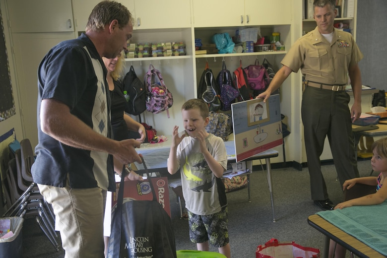 Chris Elliott, water resources manager, Natural Resources and Environmental Affairs, gives Damien Lawrence, first grader, prizes for being the second runner-up in the 2016 Earth Day Poster Contest at Twentynine Palms Elementary School June 2, 2016. (Official Marine Corps photo by Cpl. Thomas Mudd/Released)