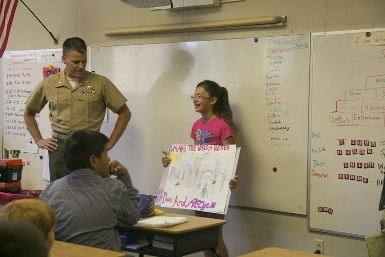 Lt. Col. Timothy Pochop, director, Natural Resources and Environmental Affairs, congratulates Nicole Doten, fifth Grader, for being one of the finalists of the 2016 Earth Day Poster Contest at Twentynine Palms Elementary School June 2, 2016. (Official Marine Corps photo by Cpl. Thomas Mudd/Released)