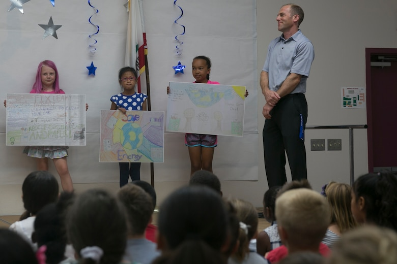 Audrey Roberts and Kecel Sabio, third Grader, and Shaylin Metcalfe, fourth grader, present their posters from the 2016 Earth Day Poster Contest at Condor Elementary School June 6, 2016. (Official Marine Corps photo by Cpl. Thomas Mudd/Released)