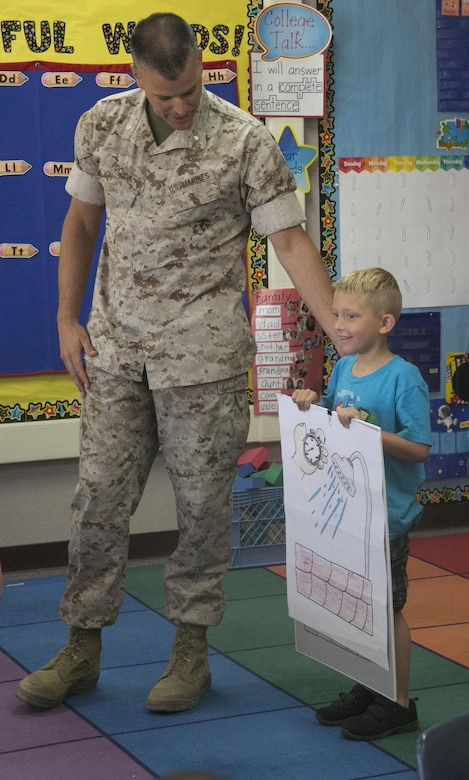 Lt. Col. Timothy Pochop, director, Natural Resource and Environmental Affairs, congratulates Christopher Halles, kindergartener, for being a finalist in the 2016 Earth Day Poster Contest at Condor Elementary School June 6, 2016. (Official Marine Corps photo by Cpl. Thomas Mudd/Released)