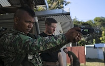 Pvt. Oldegar Gusmao (Left) fires an X26-E Taser under the instruction of Cpl. Preston G. Thompson (Right) during a non-lethal weapons course, June 7, 2016, at Metinaro, Timor Leste, as part of Exercise Crocodilo 16. The course gives Marines an opportunity to instruct Timorese soldiers on less-than-lethal methods for handling any disputes in the future. Crocodilo is a multi-national, bilateral exercise designed to increase interoperability and relations by sharing infantry, engineering, combat lifesaving and law enforcement skills. Gusmao an infantryman with Bravo Company, 1st Battalion, Timor Leste Defense Force, stationed in Baucau, Timor Leste. Thompson, from Wyoming, Michigan, is a military policeman and chief instructor for the non-lethal weapons course with Task Force Koa Moana, originally assigned to Charlie Company, 3rd Law Enforcement Battalion, III Marine Expeditionary Force.