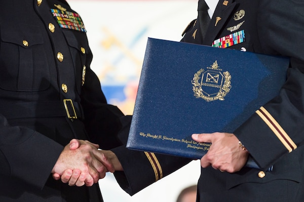 Marine Corps Gen. Joe Dunford, chairman of the Joint Chiefs of Staff, congratulates a graduate during the National Defense University's 2016 graduation ceremony at Fort Lesley J. McNair in Washington, D.C., June 9, 2016. The university provides military education to senior leaders. DoD photo by Army Staff Sgt. Sean K. Harp