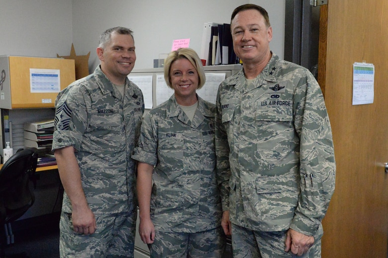 Air Force District of Washington Commander Maj. Gen. Darryl Burke, Air Force District of Washington Command Chief Master Sgt. Tommy Mazzone, and Senior Master Sgt. Jennifer Klink pose for a photo op in the dental clinic on Joint Base Anacostia-Bolling, Washington D.C., June 9, 2016. Klink was recognized by Gen. Burke for her efforts in making 2015 AFDW Annual Awards banquet a memorable event.
