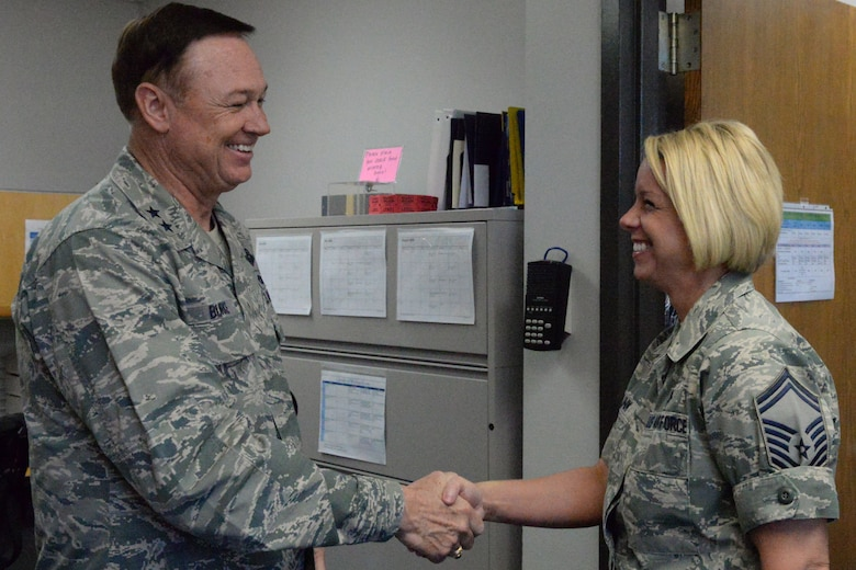Air Force District of Washington Commander Maj. Gen. Darryl Burke presents a coin to Senior Master Sgt. Jennifer Klink in the dental clinic on Joint Base Anacostia-Bolling, Washington D.C., June 9, 2016. Klink was recognized by Gen. Burke for her efforts in making 2015 AFDW Annual Awards banquet a memorable event.