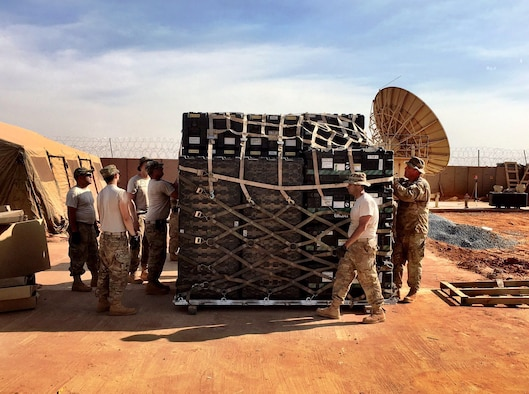 Airmen from the 1st Combat Communications Squadron prepare equipment in Africa. The Airmen replaced pallets of communications equipment for transportation as another squadron replaced the first. This was the first time an entire combat communications team and equipment were switched out. (Courtesy Photo)