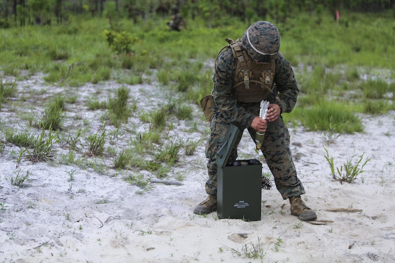 A mortarman with 1st Battalion, 2nd Marine Regiment, 2nd Marine Division, primes a mortar round before handing it off to a gunner for firing at Camp Lejeune, N.C., June 6, 2016. Marines underwent mortar familiarization and proficiency training in preparation for their upcoming deployment in support of Special-Purpose Marine Air-Ground Task Force. (U.S. Marine Corps photo by Lance Cpl. Aaron K. Fiala/Released)