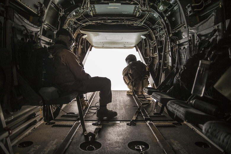 Two crew chiefs with Marine Medium Tiltrotor Squadron (VMM) 165 observe the area outside an MV-22B Osprey during a flight from Marine Corps Air Station Miramar to Marine Corps Base Camp Pendleton, Calif., June 8. Crew chiefs worked alongside Osprey pilots in order to maintain visuals for the overall flight. (U.S. Marine Corps photo by Sgt. Michael Thorn/Released)