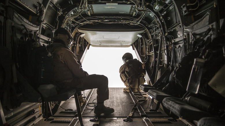 Two crew chiefs with Marine Medium Tiltrotor Squadron 165 observe the area outside an MV-22B Osprey during a flight from Marine Corps Air Station Miramar to Marine Corps Base Camp Pendleton, California, June 8. Crew chiefs worked alongside Osprey pilots in order to maintain visuals for the overall flight.