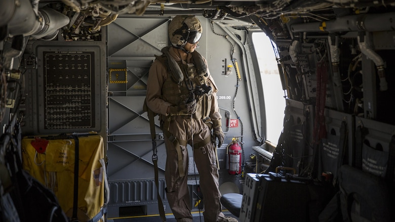 A crew chief with Marine Medium Tiltrotor Squadron 165 looks outside an MV-22B Osprey during a training flight from Marine Corps Air Station Miramar to Marine Corps Base Camp Pendleton, California, June 8. Crew chiefs aboard the Osprey assisted with maintaining visuals during the flight for the pilots.