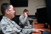A 2nd Space Warning Squadron space operator engages in a phone call in the in the Space Based Infrared System Mission Control Station Block 10 Ground System room after the ribbon cutting that began the testing and evaluation phase Oct. 2014, at Buckley Air Force Base, Colo. The system had previously been in the testing and evaluation phase, but now, the 460th Space Wing is flying operational mission satellites twenty four hours a day, seven days a week. (U.S Air Force photo by Staff. Sgt. Darren Scott/Released)
