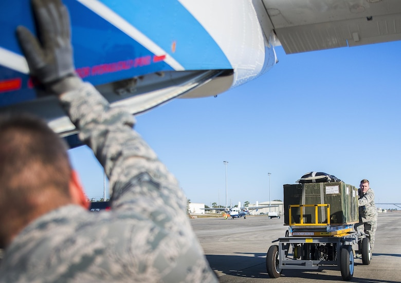 Staff Sgt. Justin Spencer, 919th Special Operations Logistics Readiness Squadron, pushes parachute bundles toward a C-145 Skytruck to be loaded for a training sortie at Duke Field, Fla.  The 300-pound bundles are loaded so new loadmasters can perform their initial airdrop training and prior-qualified Airmen can maintain proficiency.  (U.S. Air Force photo/Tech. Sgt. Sam King)