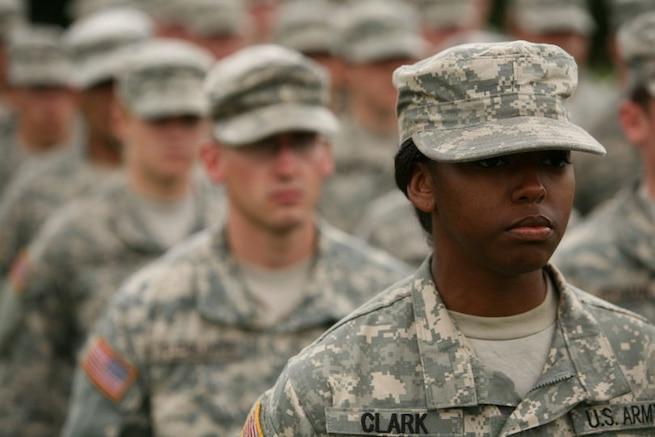 Diverse group of Soldiers wearing ACU's standing in formation outside during the day.