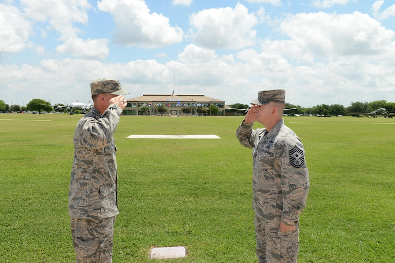 """Chief Master Sgt. Brendan Criswell, Command Chief, 24th Air Force, salutes Maj. Gen. Ed Wilson, Commander, 24th Air Force, during the chief's final reenlistment swear-in at JBSA-Lackland 10 June. Criswell, after 27 years on active duty, is scheduled to transfer in July to serve as command chief for Air Force Space Command in Colorado Springs, Colo."" (US Air Force photo by MSgt Stuart Wilson)"