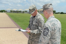 """""""Maj. Gen. Ed Wilson, Commander, 24th Air Force, signs the official reenlistment document for Chief Master Sgt. Brendan Criswell, Command Chief, 24th Air Force, during his final reenlistment swear-in at JBSA-Lackland 10 June. Criswell, after 27 years on active duty, is scheduled to transfer in July to serve as command chief for Air Force Space Command in Colorado Springs, Colo."""" (US Air Force photo by MSgt Stuart Wilson)"""