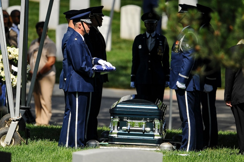 Chaplain (Maj.) Kevin Hudson conducts the final inspection of former 2nd Lt. Malvin G. Whitfield's flag before presenting it to his wife, Nola, at a graveside ceremony at Arlington National Cemetery, Va., June 8, 2016. Whitfield died Nov. 19, 2015, at the age of 91. (U.S. Air Force photo/Tech. Sgt. Bryan Franks)