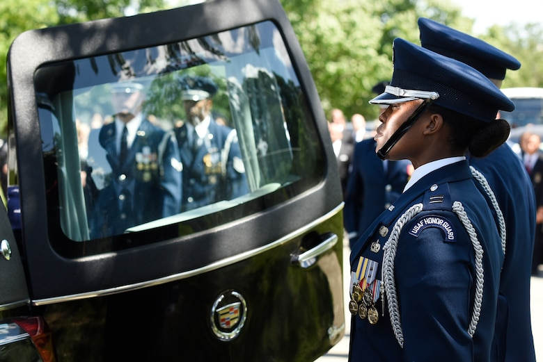 Capt. Kendra Gusme, a member of the U.S. Air Force Honor Guard, stands at attention while the casket carrying former 2nd Lt. Malvin G. Whitfield, an Army Air Forces and Air Force veteran, is removed from a hearse at Arlington National Cemetery, Va., June 8, 2016. Whitfield served in the Army Air Forces as a Tuskegee Airman, and later joined the Air Force Reserve as an officer. The honor guard provided full honors during the graveside service. (U.S. Air Force photo/Staff Sgt. Alyssa C. Gibson)