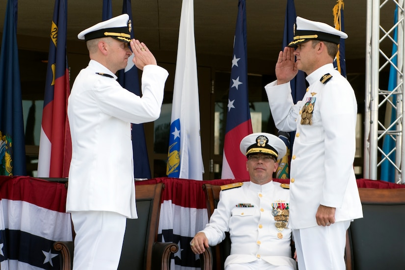 Commander Brett Pugsley (right) takes command of the Naval Consolidated Brig Charleston with a salute to his predecessor, Cmdr. J. Michael Cole, while Rear Adm. David Steindl, Commander of Navy Personnel Command, observes during a change of command ceremony June 10, 2016, at Joint Base Charleston S.C. Pugsley was previously the Brig's executive officer. Cole who commanded the Brig for three years is retiring after 20 years of service. (U.S. Air Force photo/Staff Sgt. Jared Trimarchi)