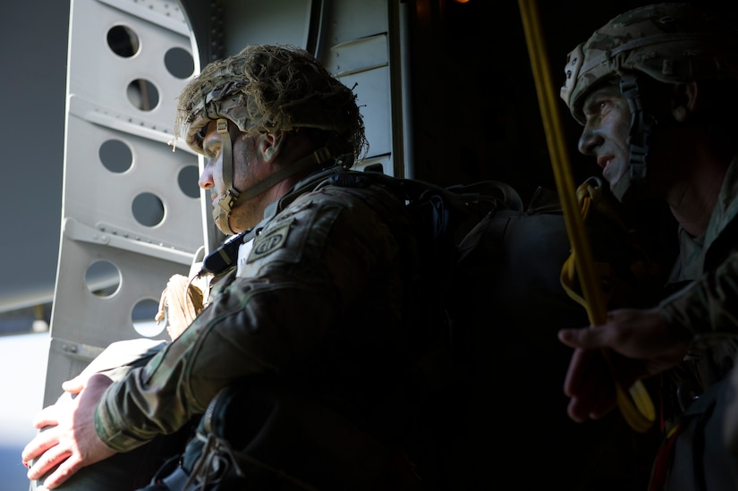 A Solider from the 82nd Airborne Division positions himself in front of the jump door while his jumpmaster looks on during an airdrop into Poland during Exercise Swift Response June 7, 2016. Cargo and U.S. Army and allied parajumpers were dropped into Poland as part of the exercise. Training alongside allies and fellow services allows AMC Airmen to prepare to execute rapid global mobility missions at any moment to any location in the world. (U.S. Air Force photo/Staff Sgt. William A. O'Brien)