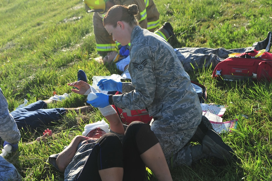 U.S. Air Force Senior Airman Katelyn Potts, an aerospacial medical technician assigned to the 509th Medical Operations Squadron, applies medical aid to a simulated aircraft accident victim during a major accident response exercise (MARE) at Whiteman Air Force Base, Mo., June 8, 2016. Firefighters and other emergency response personnel conducted the MARE to prepare for any mishaps that may occur in real-world situations.  (US Air Force photo by Senior Airman Jovan Banks)