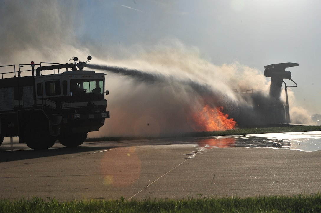 Firefighters from the 509th Civil Engineer Squadron move their fire engine into position to extinguish a simulated aircraft fire during a major accident response exercise (MARE) at Whiteman Air Force Base, Mo., June 8, 2016. Firefighters and other emergency response personnel conducted the MARE to prepare for any mishaps that may occur in real-world situations. (US Air Force photo by Senior Airman Jovan Banks)