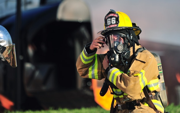 A firefighter from the 509th Civil Engineer Squadron makes adjustments to his gear prior to engaging with a simulated aircraft fire during a major accident response exercise (MARE) at Whiteman Air Force Base, Mo., June 8, 2016. The exercise is conducted to test readiness and response times in case of a major accident.  (US Air Force photo by Senior Airman Jovan Banks)