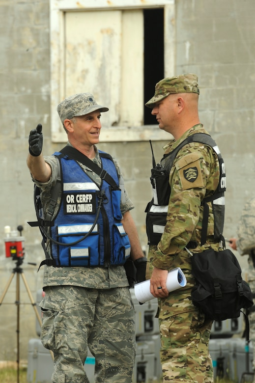 Oregon Air National Guard Lt. Col. Alex Charney-Cohen, left, and Oregon Army National Guard Lt. Col. Michael Moffit, CERFP commander, right, confers the set up area for equipment and materials in the exercise village at Camp Rilea during Cascadia Rising exercise, Warrenton, Ore., June 9, 2016. Cascadia Rising scenario is a 9.0 magnitude earthquake along the Cascadia Subduction Zone (CSZ) resulting in a tsunami, testing first responders, emergency management and public safety officials in the Pacific Northwest. (U.S. Air National Guard photo by Tech. Sgt. John Hughel, 142nd Fighter Wing Public Affairs/Released)