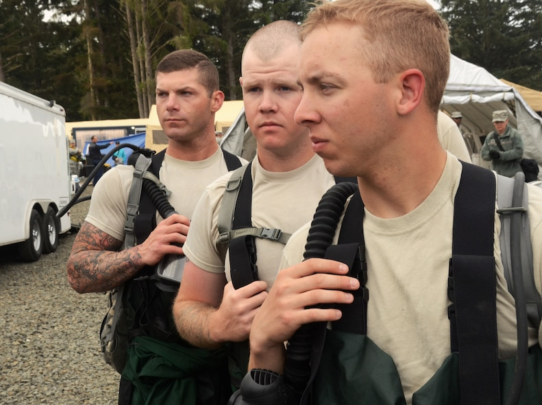 There Army CBRNE Enhanced Force Response Force Package (CERFP) members from the Oregon and Kentucky National Guard wait to entry a training area together during the Cascadia Rising exercise at Camp Rilea, Warrenton, Ore., June 7, 2016. Cascadia Rising scenario is a 9.0 magnitude earthquake along the Cascadia Subduction Zone (CSZ) resulting in a tsunami, testing first responders, emergency management and public safety officials in the Pacific Northwest. (U.S. Air National Guard photo by Tech. Sgt. John Hughel, 142nd Fighter Wing Public Affairs/Released)