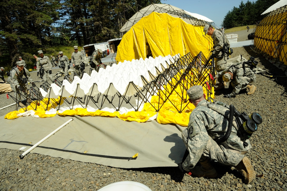 The CBRNE Enhanced Force Response Force Package (CERFP) members from the Oregon and Kentucky National Guard work together to set up medical faculties during the Cascadia Rising exercise at Camp Rilea, Warrenton, Ore., June 7, 2016. Cascadia Rising scenario is a 9.0 magnitude earthquake along the Cascadia Subduction Zone (CSZ) resulting in a tsunami, testing first responders, emergency management and public safety officials in the Pacific Northwest. (U.S. Air National Guard photo by Tech. Sgt. John Hughel, 142nd Fighter Wing Public Affairs/Released)