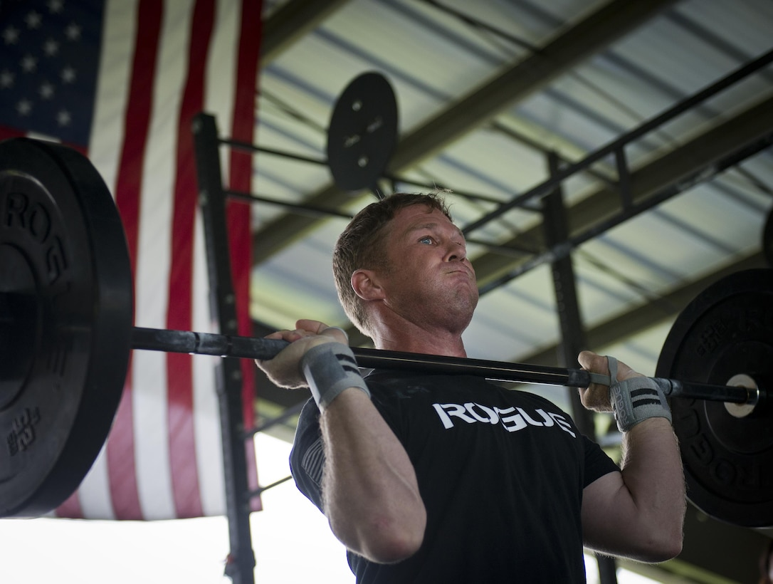 Devin Widdoes, 7th Special Forces Group, prepares to lift weights over his head during a team combat fit competition June 11 at Duke Field, Fla.  The three-round competition pushed the teams to their limits with repetitive weight lifting, rowing, sled-pulling and other kinetic activities.  (U.S. Air Force photo/Tech. Sgt. Sam King)