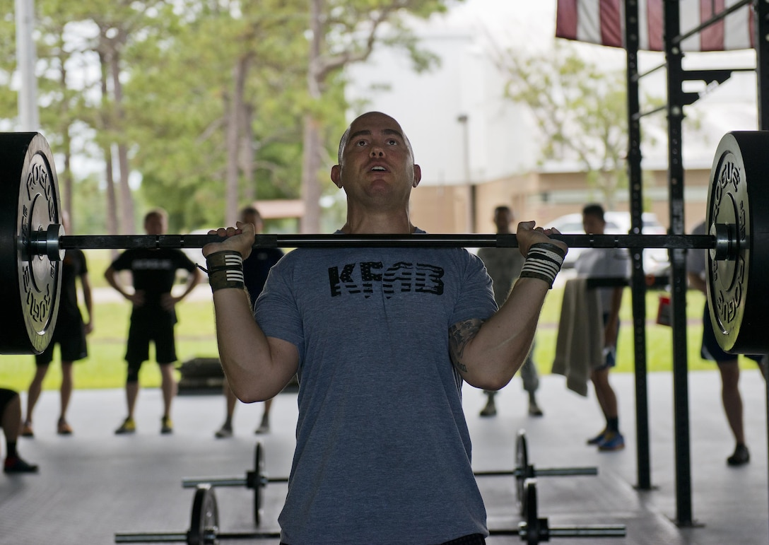 Tech. Sgt. Andrew Knudsen, 919th Special Operations Maintenance Group, prepares to lift weights over his head during a team combat fit competition June 11 at Duke Field, Fla.  The three-round competition pushed the teams to their limits with repetitive weight lifting, rowing, sled-pulling and other kinetic activities.  (U.S. Air Force photo/Tech. Sgt. Sam King)