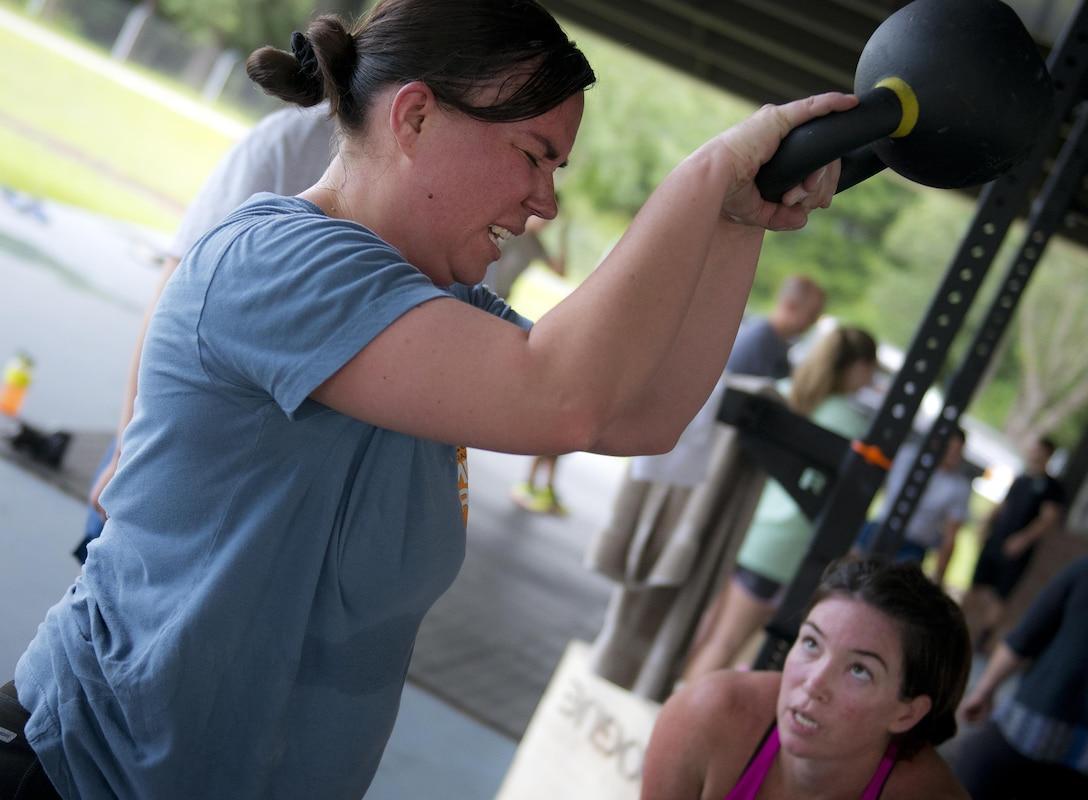 Tech. Sgt. Amanda King, 919th Special Operations Civil Engineer Squadron, struggles to lift a kettlebell over her head during a team combat fit competition June 11 at Duke Field, Fla.  The three-round competition pushed the teams to their limits with repetitive weight lifting, rowing, sled-pulling and other kinetic activities.  (U.S. Air Force photo/Tech. Sgt. Sam King)