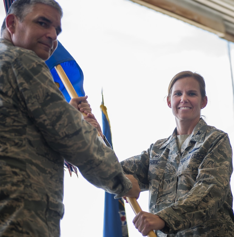 Col. Regina Sabric accepts the guidon from Col. James Phillips, the 919th Special Operations Wing commander, at the 919th Special Operations Group's change of command ceremony June 12 at Duke Field, Fla.  Sabric was stationed at the Pentagon before becoming the first female commander of the group.  (U.S. Air Force photo/Tech. Sgt. Sam King)
