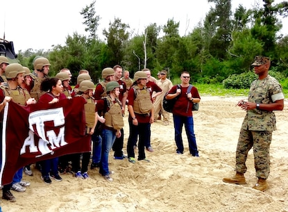 Battalion Commander Lt. Col. Carlos T. Jackson, right, addresses Texas A&M Corps of Cadets visitors on the Amphibious Assault Vehicle capability provided by Combat Assault Battalion in support of the 3rd Marine Division, May 18, 2016, at Camp Schwab, Okinawa, Japan. The Cadets visited Okinawa as part of a scholarship program which provides students the opportunity to tour military installations to learn about different occupational specialties and duty stations. This is the first time Texas A&M Corps of Cadets visited Okinawa.
